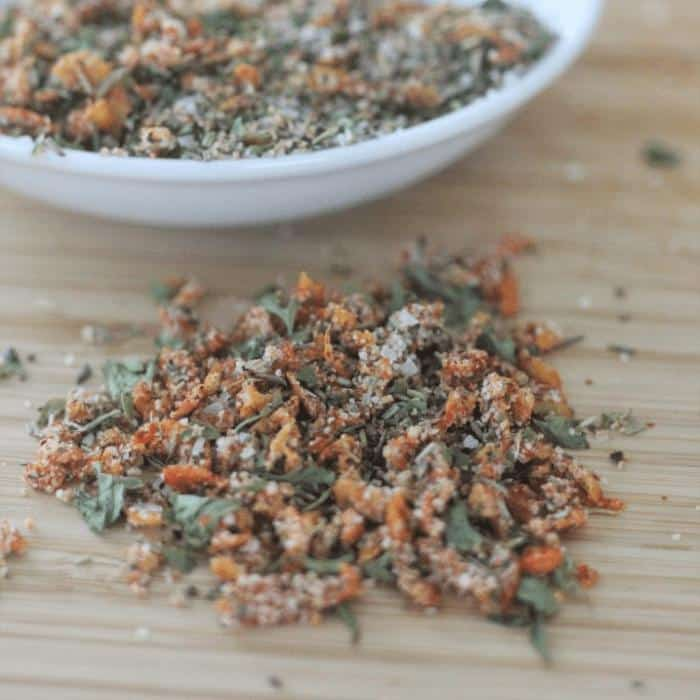 Pile of lemon herb chicken seasoning on a wooden cutting board with a white bowl of the same seasoning in the background.