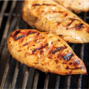 Two marinated whole grilled chicken breasts on the grill grates of a gas grill.