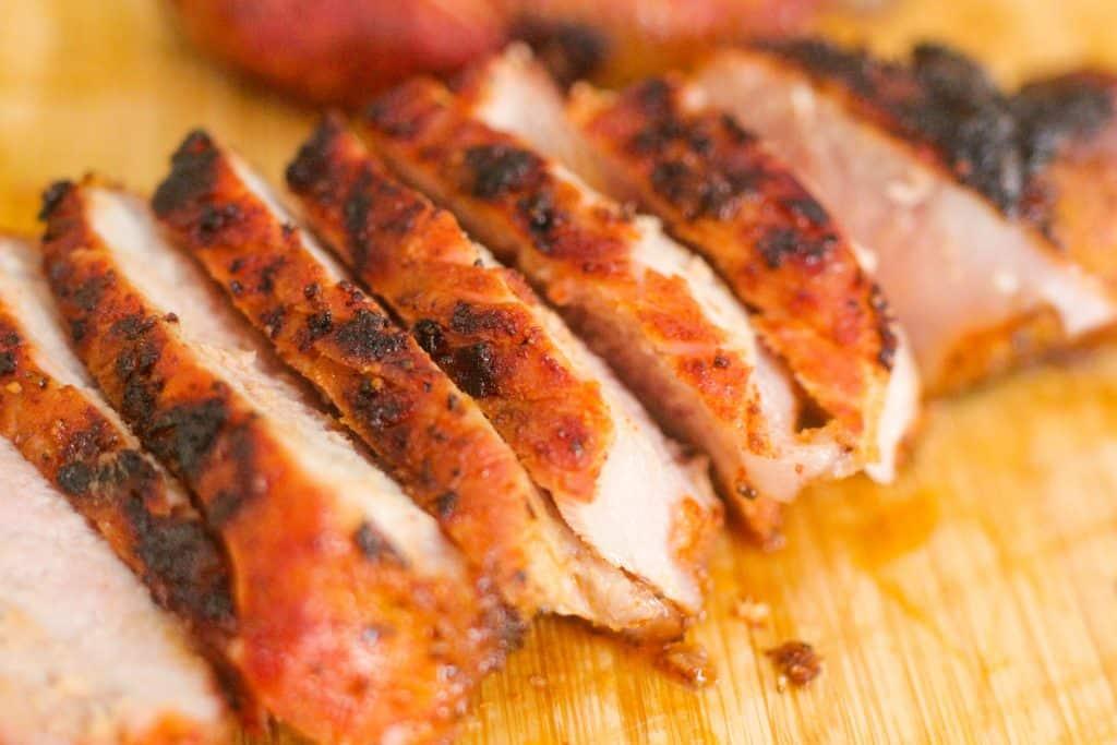 pork chops sliced on a cutting board.