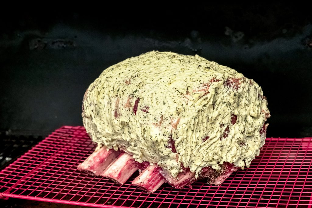 3 bone raw prime rib roast that is smothered in garlic butter. It is sitting on a roasting rack above a sheet pan in the smoker.