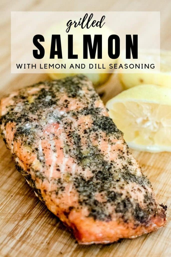 grilled salmon with lemon and dill seasoning next to sliced lemons on a wooden cutting board.