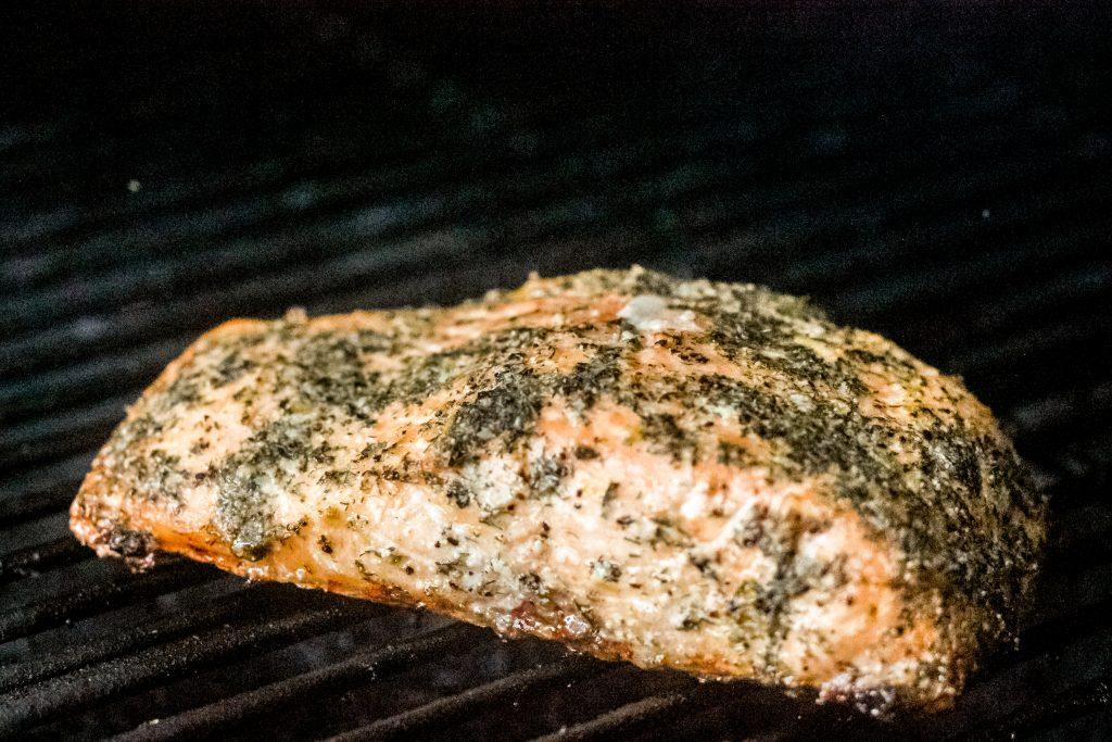 seasoned salmon fillet on grill grates.