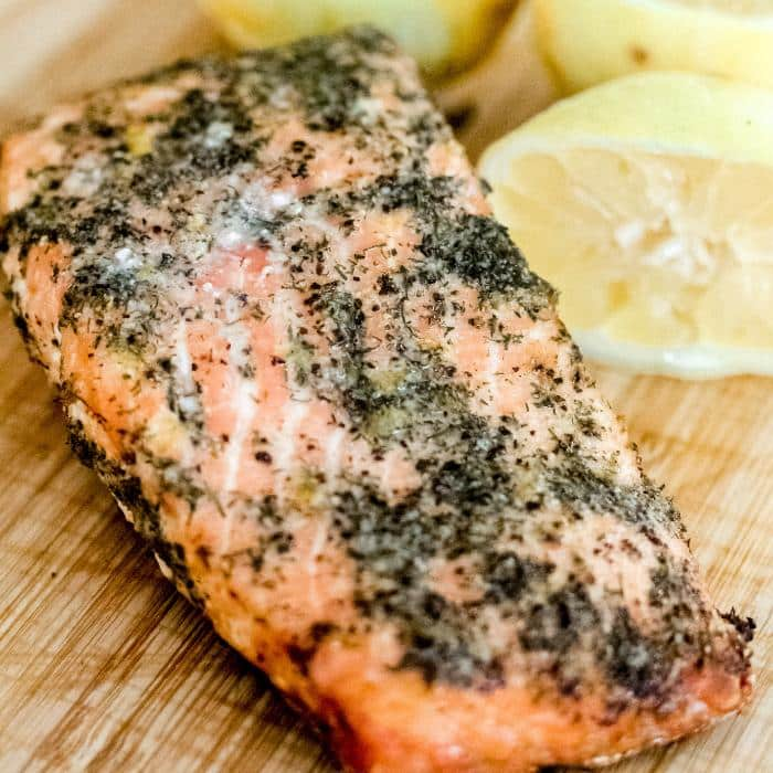 grilled salmon with a lemon dill seasoning on a wooden cutting board with sliced lemon halves in the background