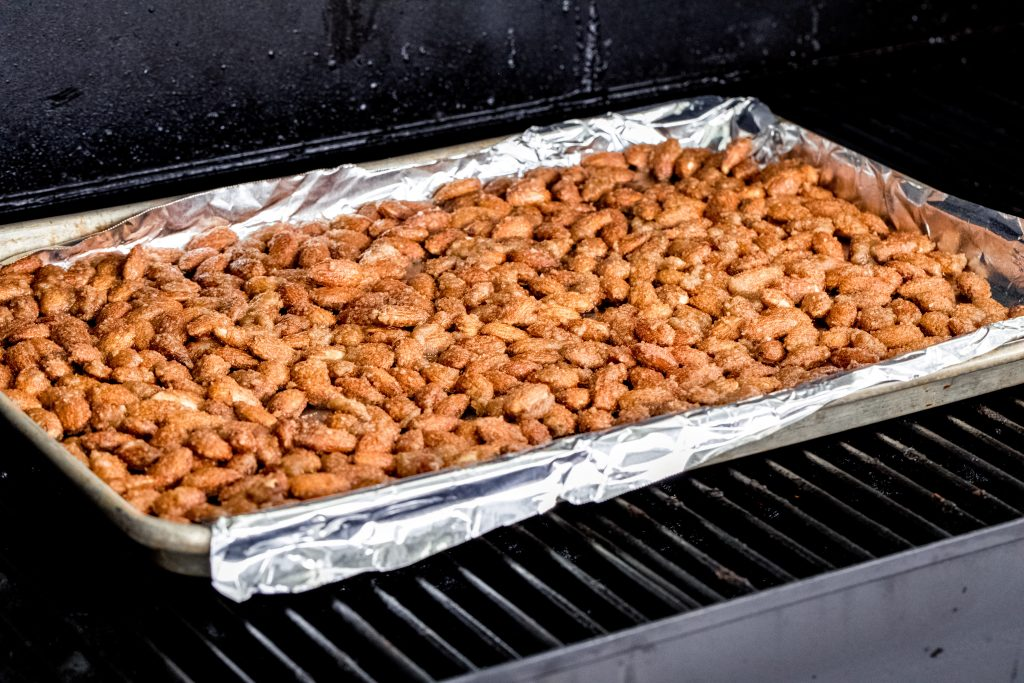 Cinnamon Almonds on a tray on the grill grate in the smoker.