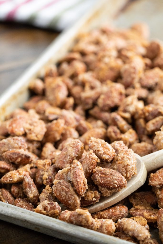 Cinnamon Almonds on a baking sheet being scooped up by a wooden spoon.