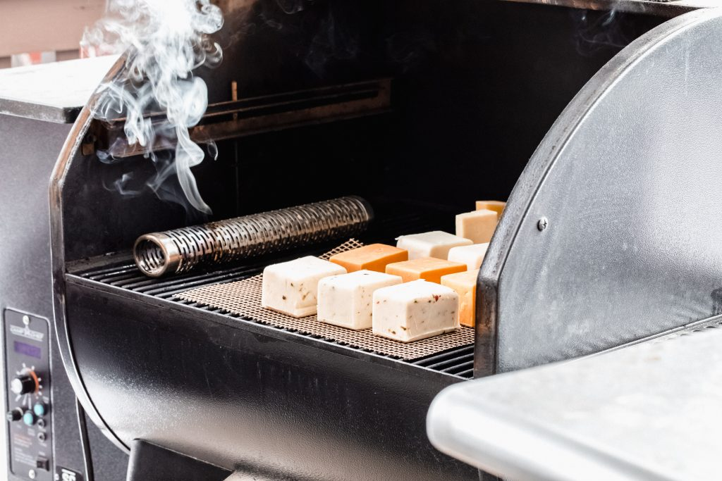 Slices of cheese on a tray inside the grill, next to a metal tube emitting smoke.