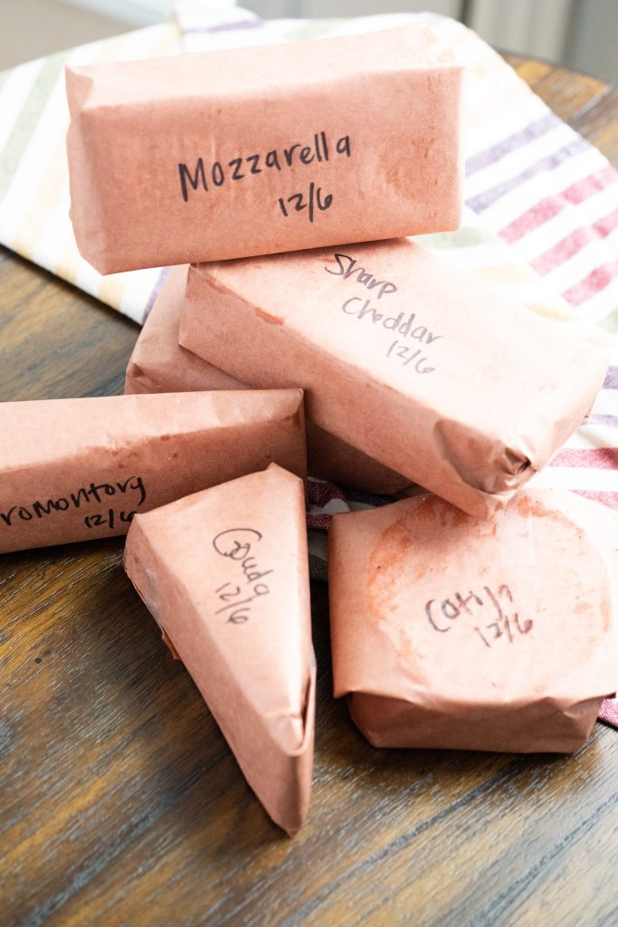 Smoked cheese wrapped in butcher paper with each package labeled with the types of cheese.