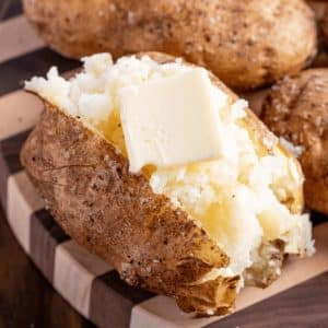 Sliced and fluffed smoked baked potato garnished with a pad of butter, salt, and pepper.