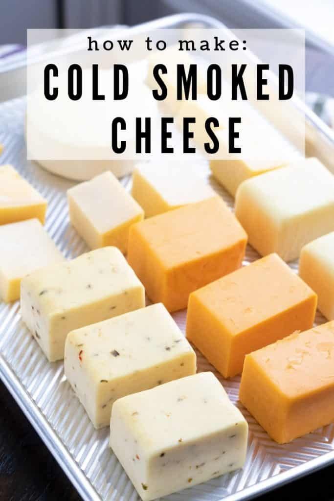 """Three different types of cheeses cut into chunks and arranged on a metal tray. Text overlay reads, """"How to make: Cold Smoked Cheese."""""""
