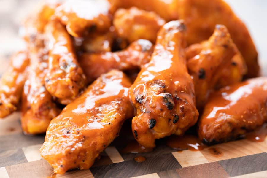 smoked chicken wings covered in Buffalo sauce on a wooden cutting board