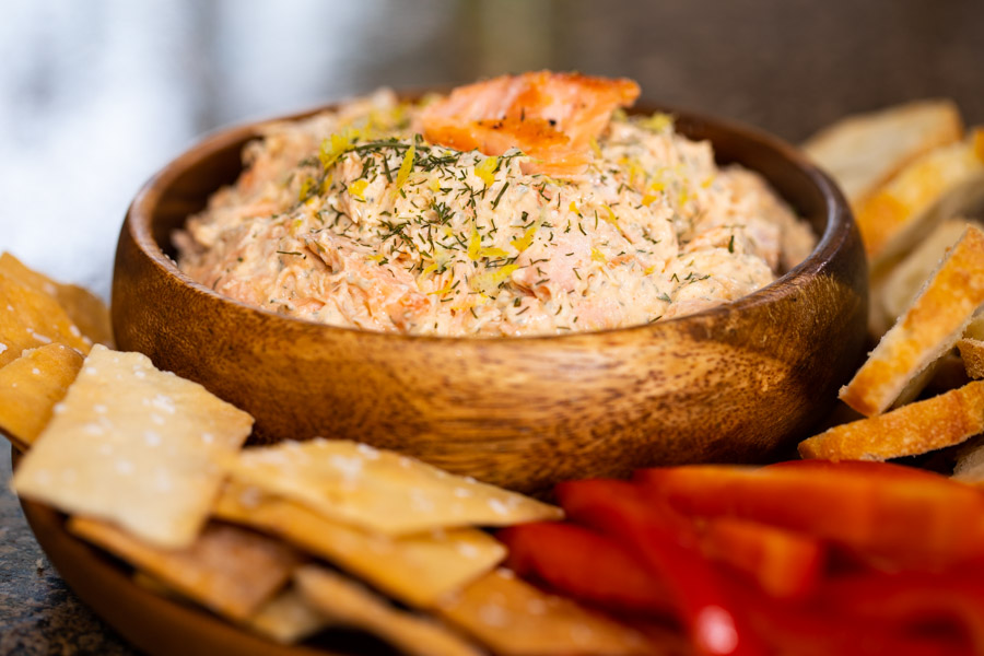 smoked salmon dip in a wooden bowl on a platter with crackers, baguettes, and fresh red bell peppers.