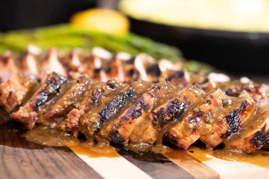 grilled pork tenderloin with beer and mustard sauce on a wooden cutting board.