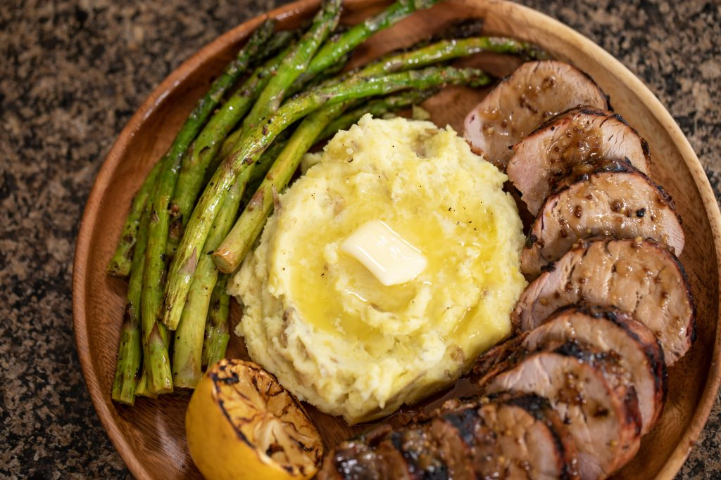 Smoked mashed potatoes on plate with smoked asparagus and pork tenderloin.