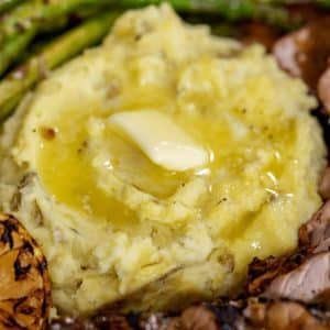 Pad of butter melting into smoked mashed potatoes surrounded by asparagus and sliced pork tenderloin.