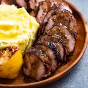 Sliced grilled pork tenderloin arranged on a wood plate next to mashed potatoes