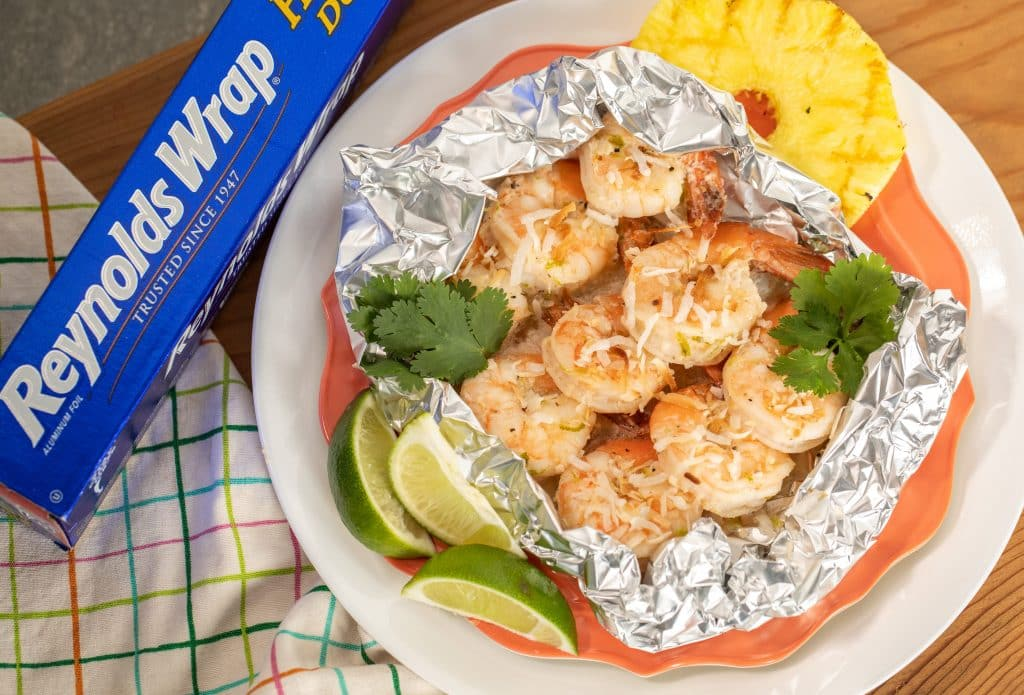 grilled coconut shrimp in foil packet with lime and grilled pineapple next to a package of Reynolds wrap aluminum foil.
