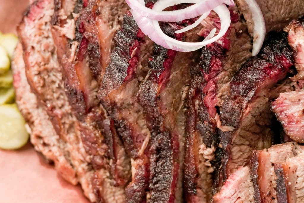 Close up of sliced brisket topped with red onions and sliced pickles in the background on pink butcher paper.