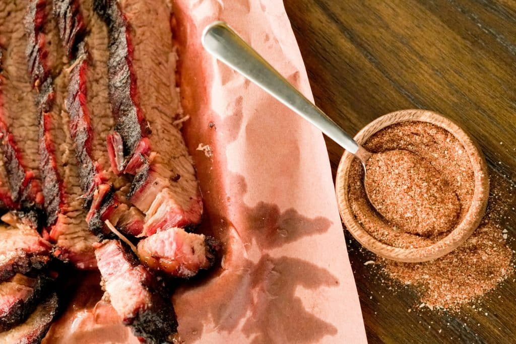 Coffee dry rubbed brisket sliced and resting on peach butcher paper next to a wooden bowl full of coffee dry rub.