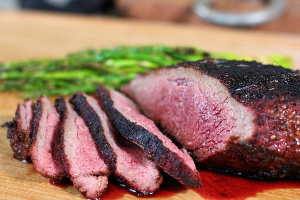 Sliced coffee rubbed tri-tip steak on a wood cutting board with grilled asparagus in the background.