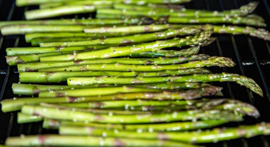 Fresh asparagus seasoned and on the grill.