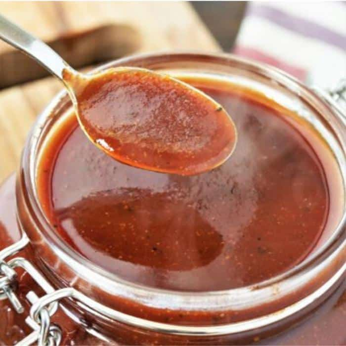 Spoonful of coffee BBQ sauce over a hinged glass mason jar of coffee BBQ sauce.