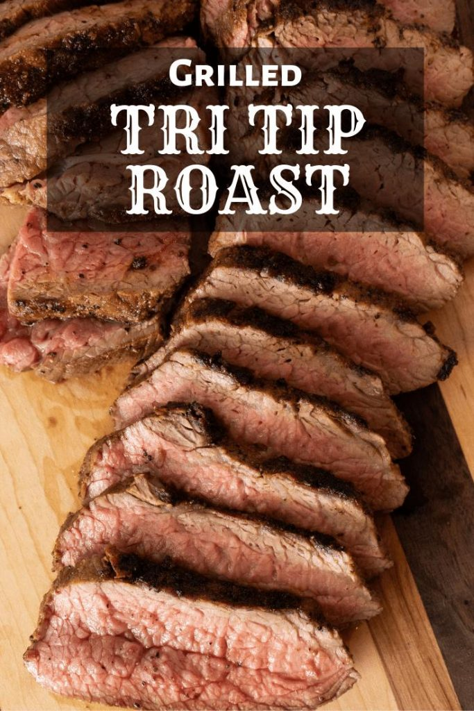 sliced tri tip roast on a wooden cutting board.