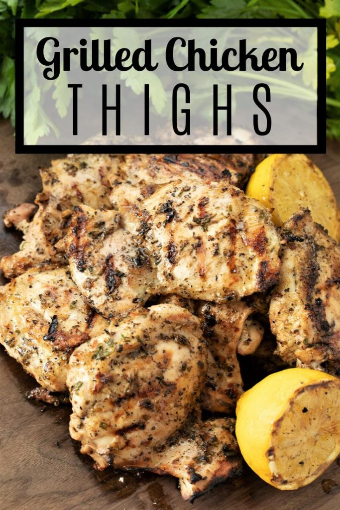grilled chicken thighs on a plate with fresh lemons.