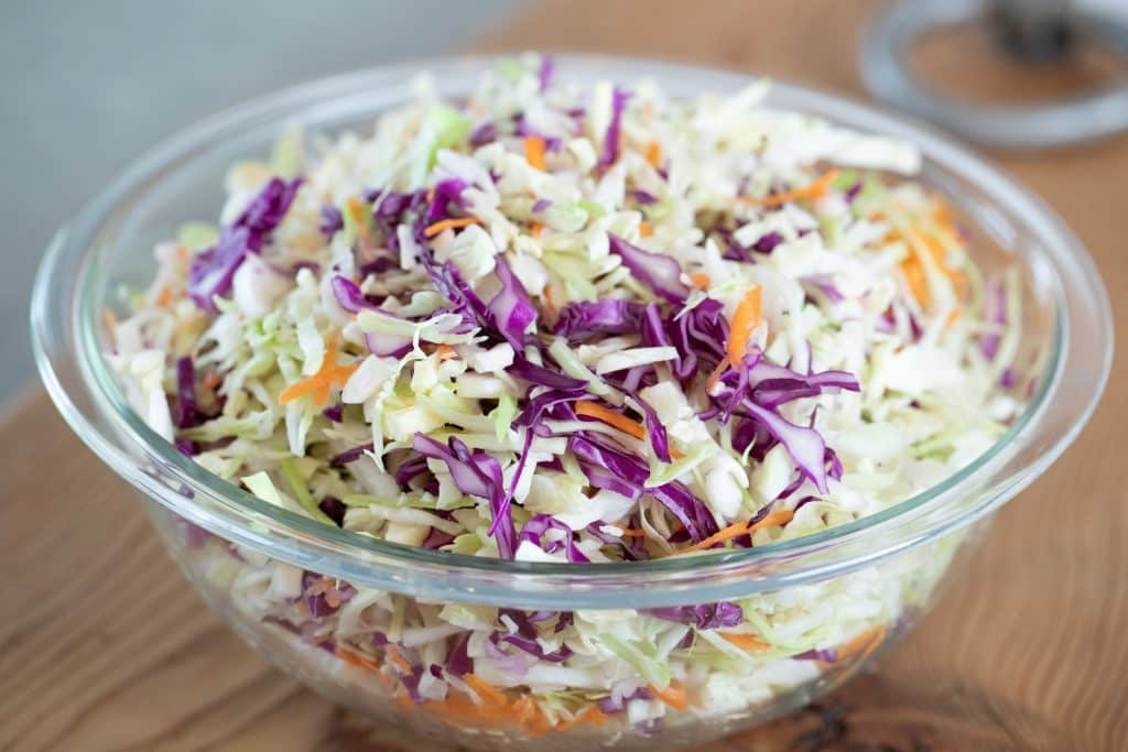 bowl of chopped green and red cabbage, onions, and carrots
