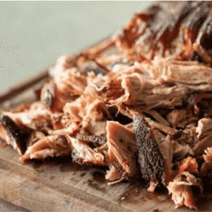 Shredded Carolina style pulled pork on a wooden cutting board.