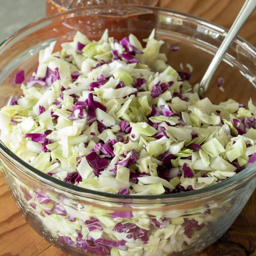 glass bowl of chopped coleslaw with vinegar dressing.