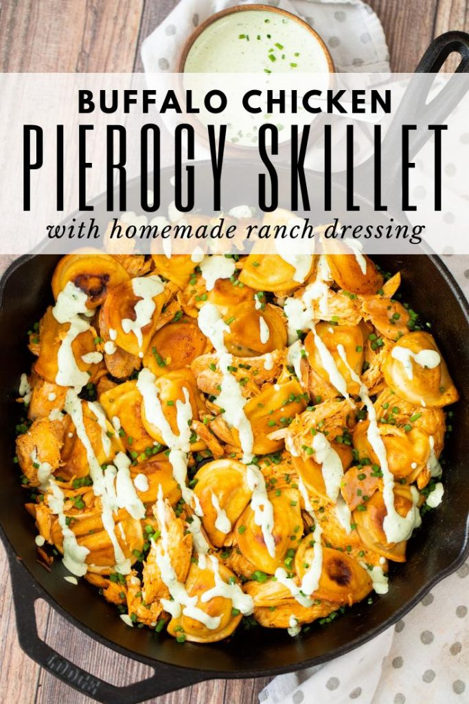 buffalo chicken pierogies in a cast iron skillet with a bowl of ranch dressing on the side.