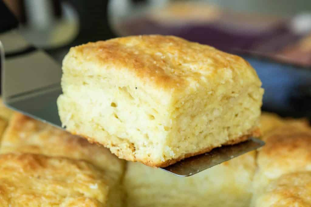 close up picture of a baked buttermilk biscuit on a spatula.