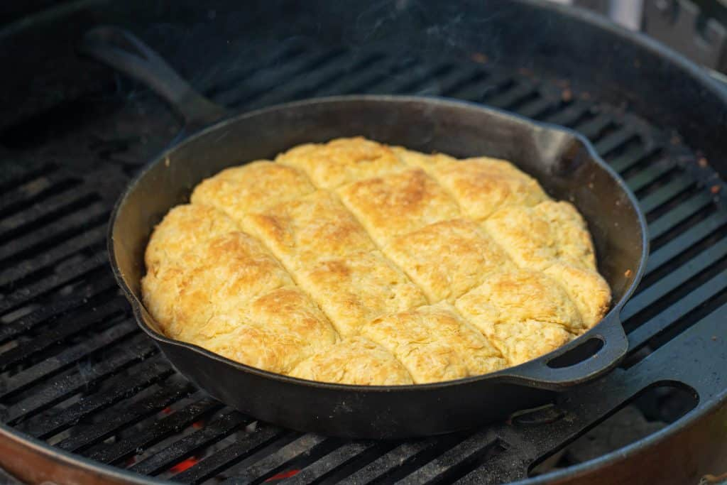 cast iron skillet with biscuits on a charcoal grill.