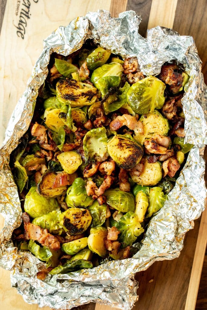 Overhead shot of Grilled Brussels and bacon in tinfoil. Displayed on a wood cutting board.