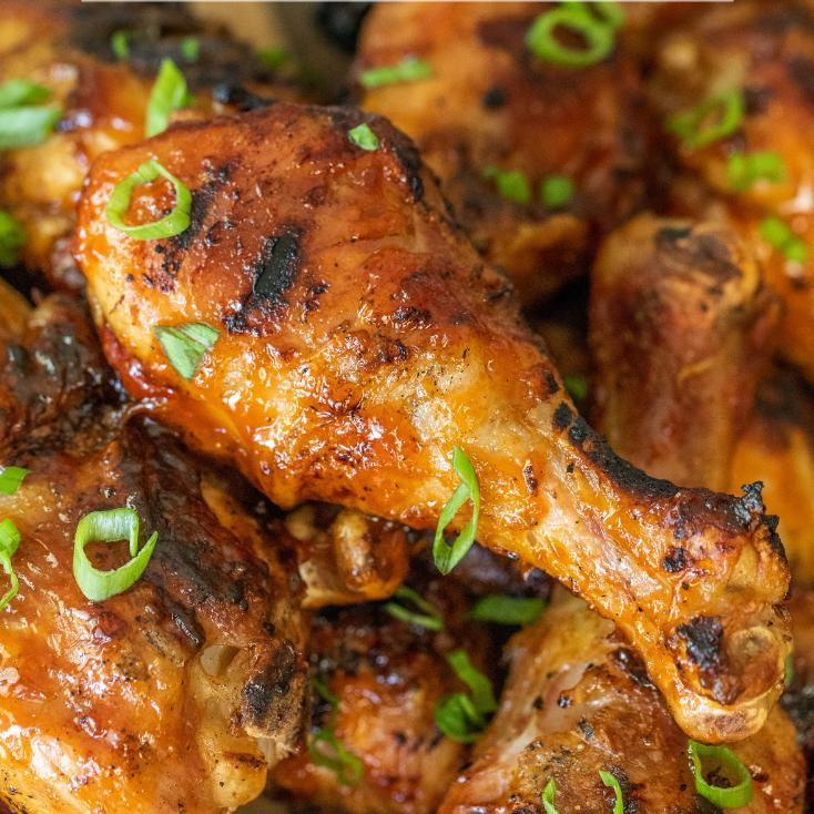 closeup of a grilled chicken drumstick covered in BBQ sauce.