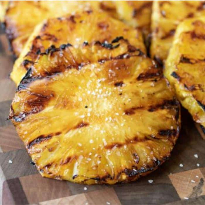 grilled pineapple slices on a wooden cutting board