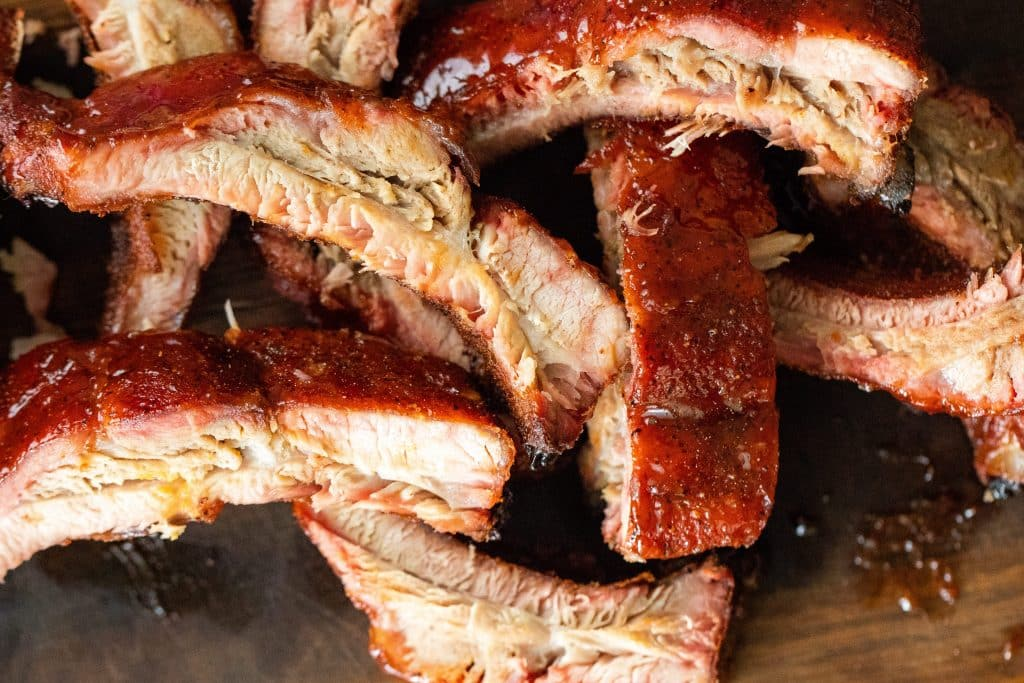 Sliced smoked ribs piled up on a wood cutting board.