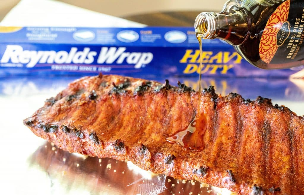 Partially cooked rack of ribs, meat side down, on a sheet of heavy duty foil with maple syrup bring drizzled onto the rib bones.