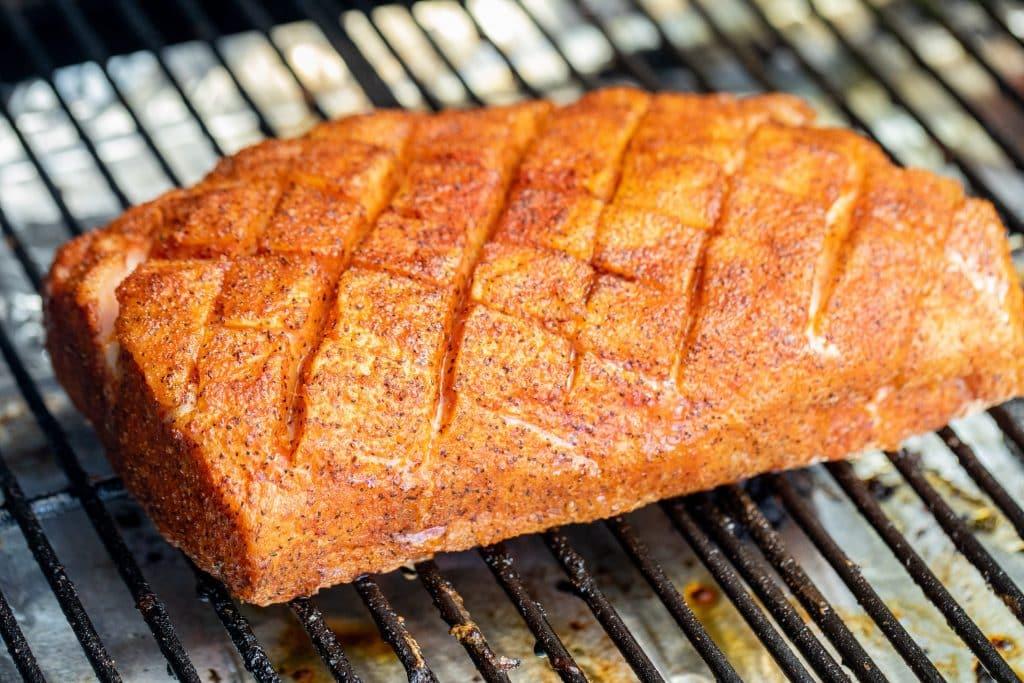 seasoned and scored pork loin on the smoker.