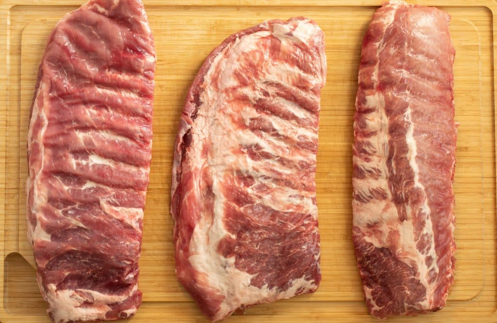 three different types of pork ribs on a wood cutting board.