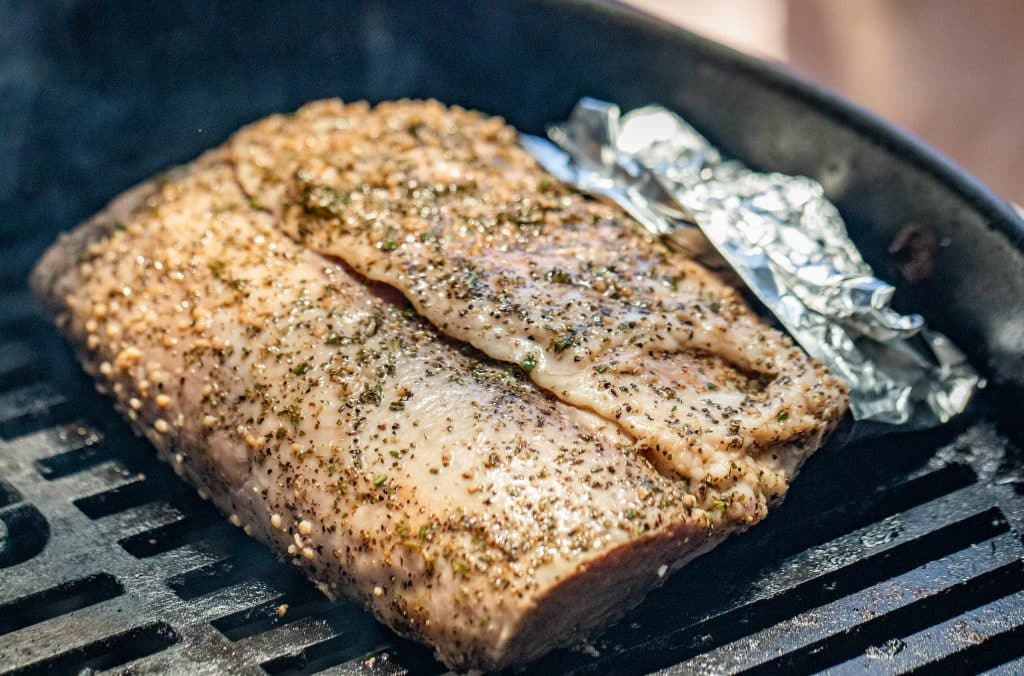 seasoned rack of lam on a grill with aluminum foil on the bones sitting on grill grates.