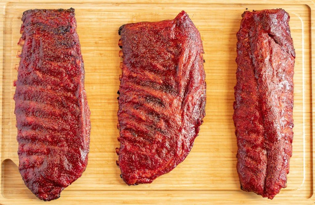 3 racks of smoked pork ribs laying flat on a wood cutting board