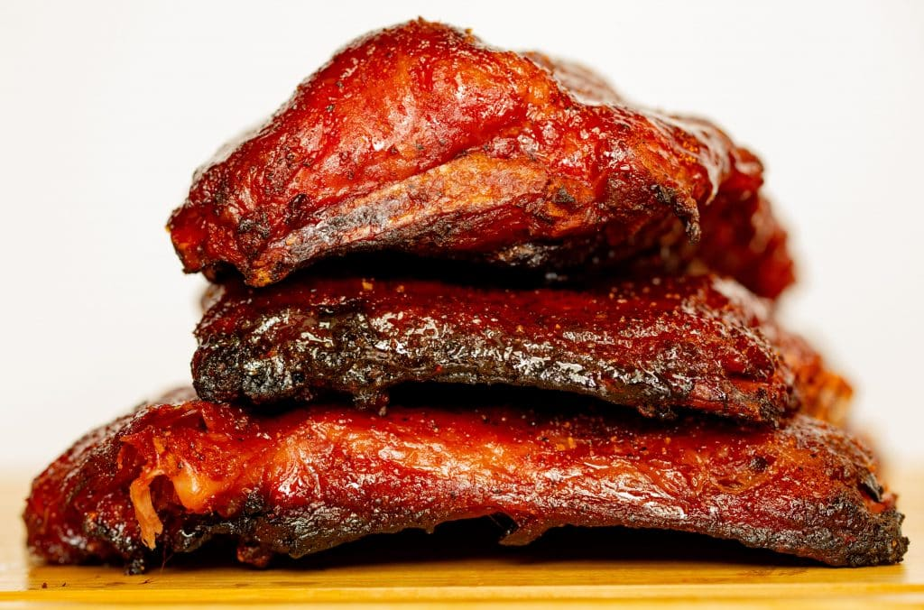 3 racks of smoked pork ribs stacked on top of each other on a wooden serving platter.