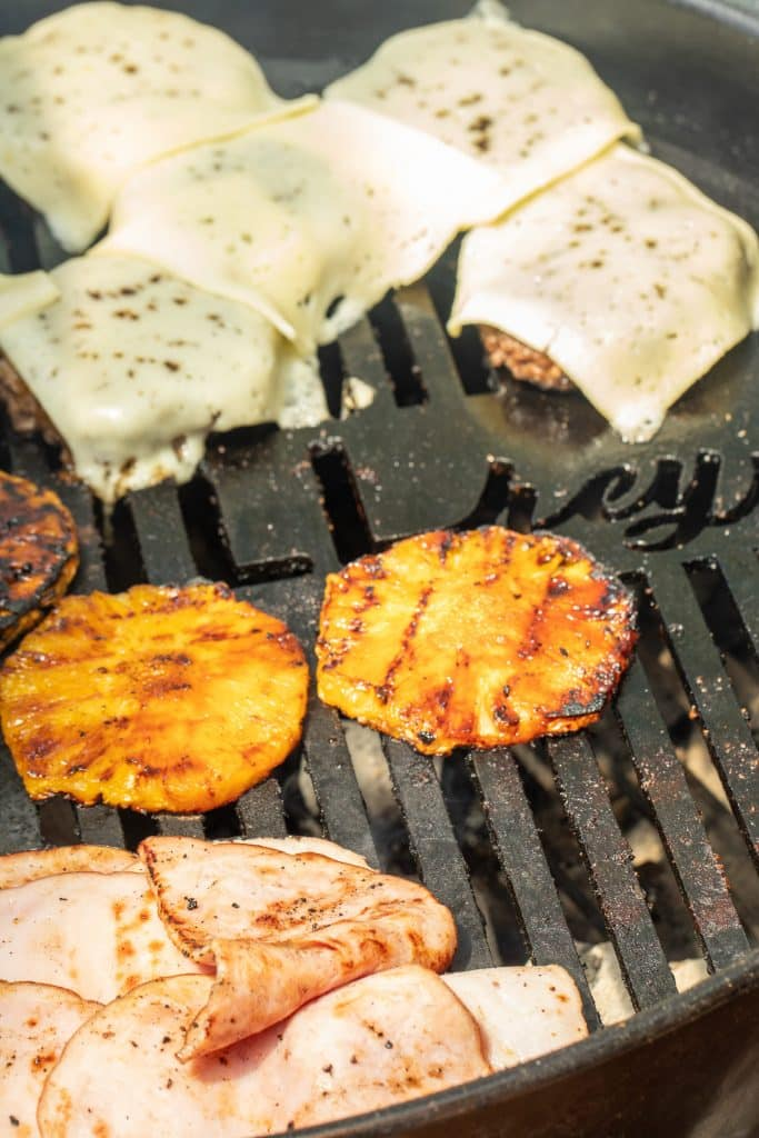 Cheese topped burger patties on the grill with grilled pineapple and ham