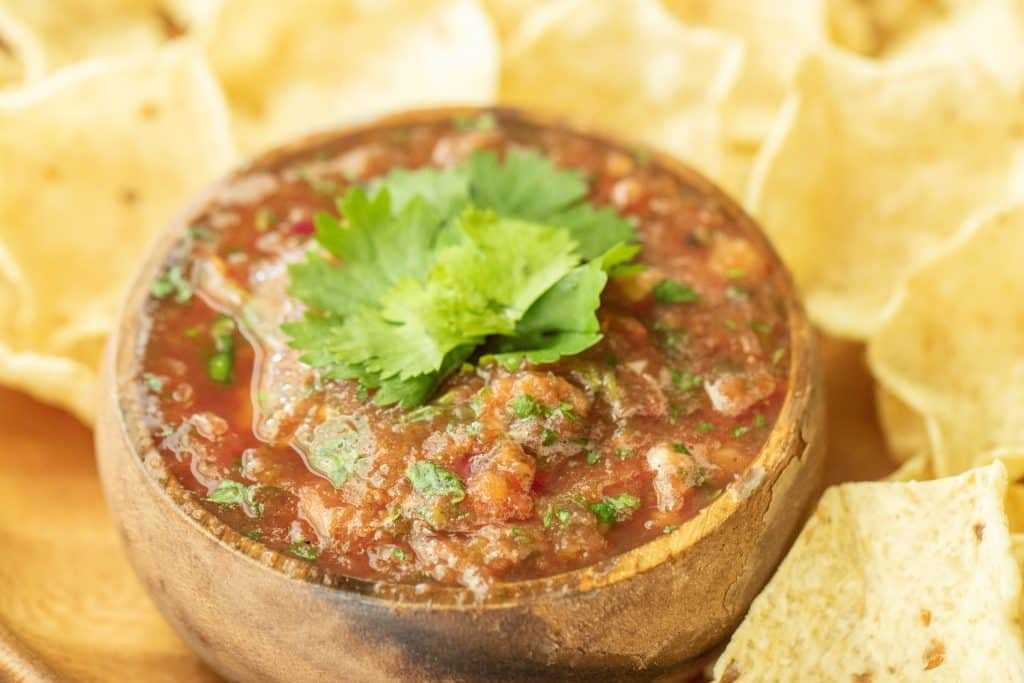 wooden bowl full of smoked salsa, surrounded by a plate of tortilla chips.