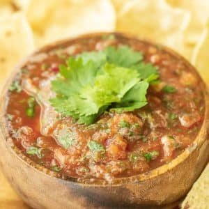 Smoked salsa garnished with fresh cilantro in a round wooden bowl surrounded by corn tortilla chips.