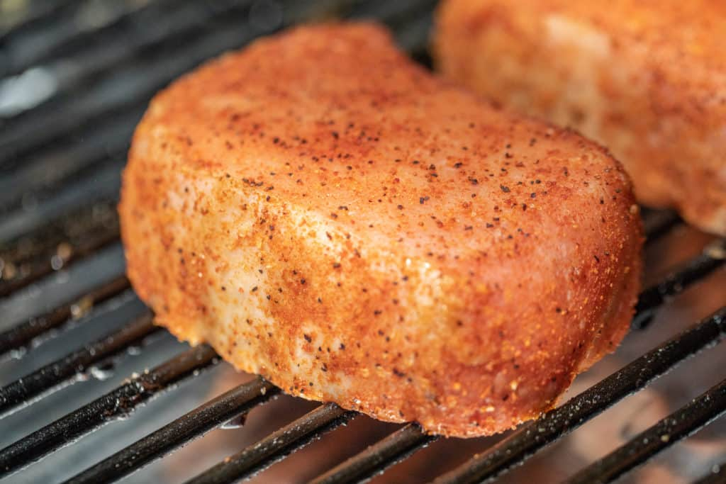 pork chop with seasoning on the grates of a smoker.