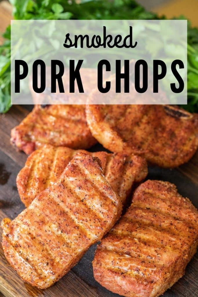 """5 smoked pork chops on a wood cutting board with parsley. Text overlay reads """"smoked pork chops."""""""