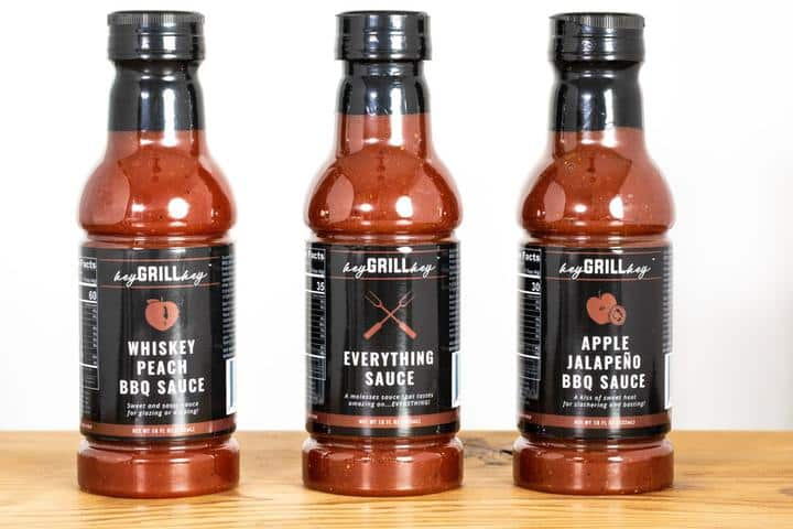 three 18-fl oz bottles of Whiskey Peach BBQ Sauce, Everything Sauce, and Apple Jalapeno Sauce on a wooden table.