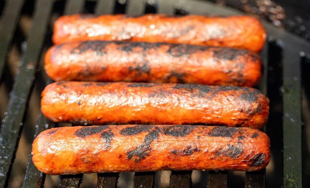 Hot dogs cooking on a charcoal grill.
